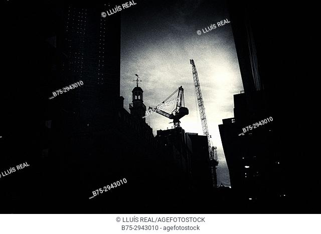 Silhouettes of building and cranes at dusk. City of London, London, England