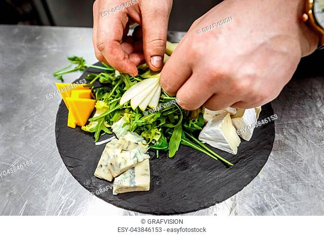 Chef garnishing cheese platter with sliced pear