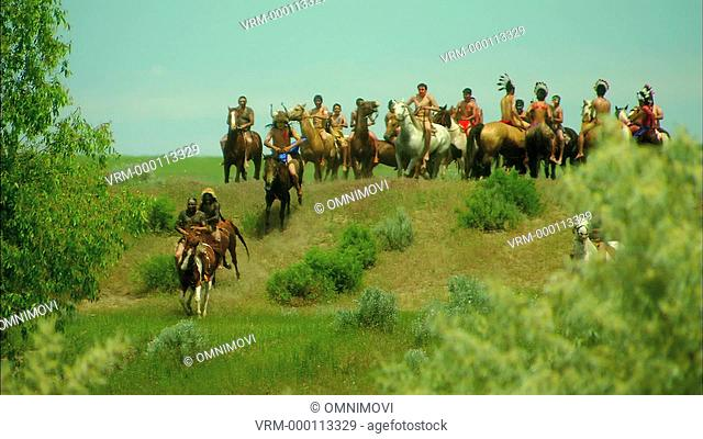 Large group of Native American Indians riding horses through countryside