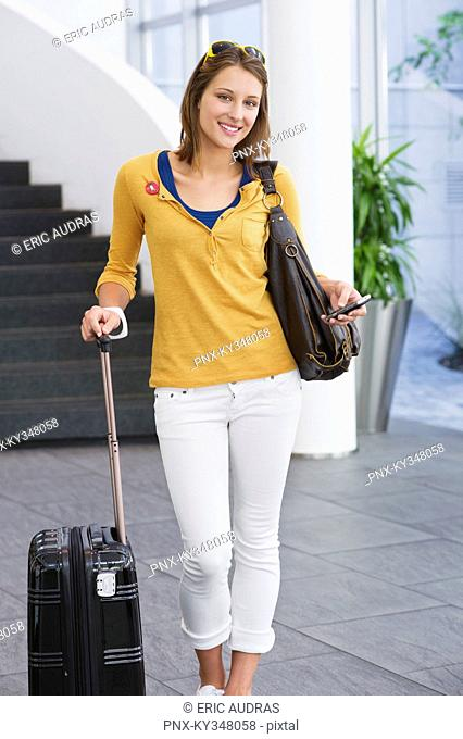 Portrait of a woman holding a mobile phone and a trolley bag