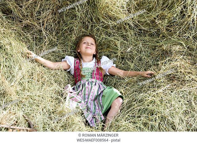 Germany, Bavaria, Girl in traditional dirndl lying in hay