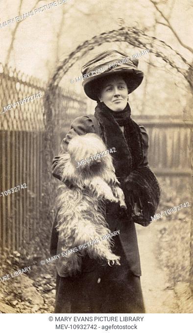 Edwardian woman holding a terrier in a garden