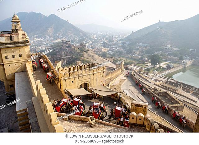 Elephants carry tourists up a stone passage to the Amer Fort in Jaipur, India