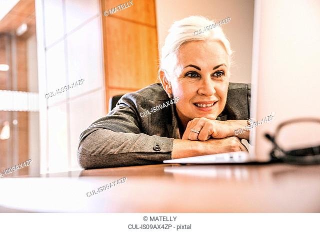 Woman leaning against desk chin on hands looking at laptop smiling