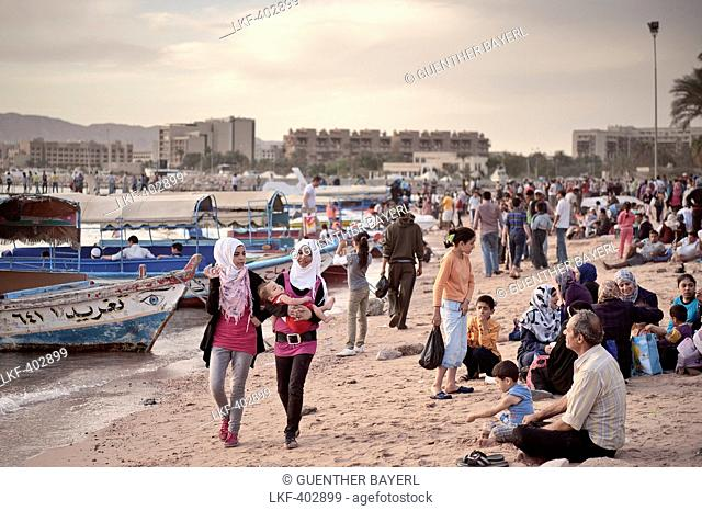 Young Jordanian woman with baby at crowded beach, Gulf of Aqaba, Red Sea, Jordan, Middle East, Asia