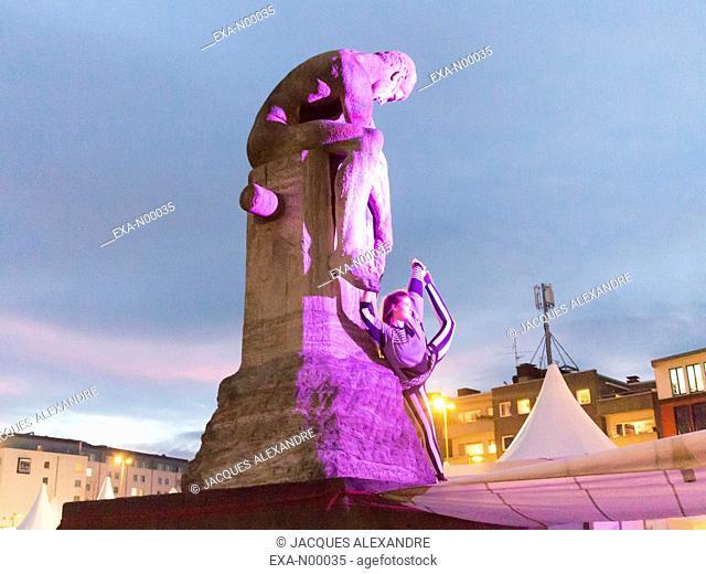 woman doing urban yoga exercises at night on a purple illuminated monument