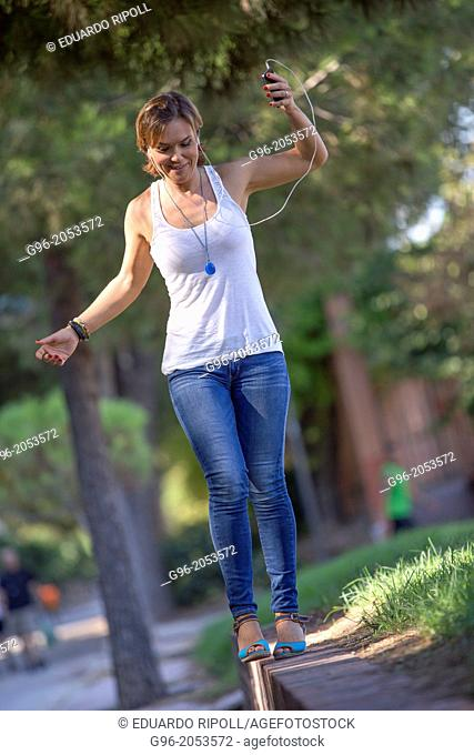 Woman listens music with earphones in a park