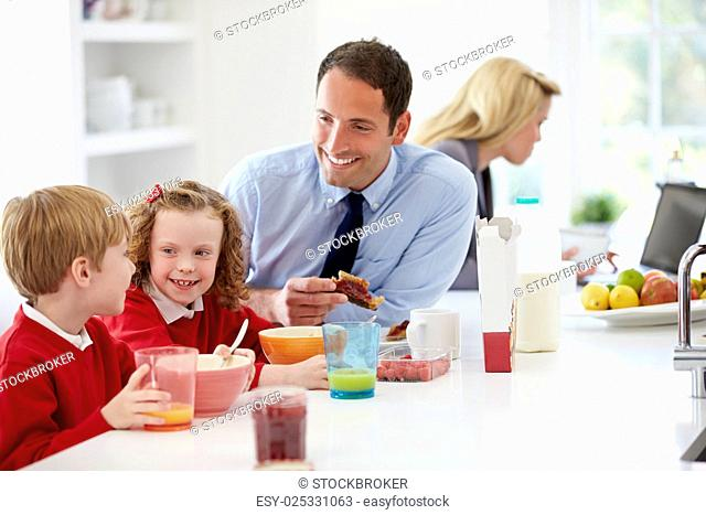 Family Having Breakfast In Kitchen Before School And Work