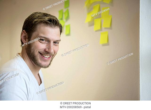 Businessman smiling with sticking adhesive notes on wall, Bavaria, Germany