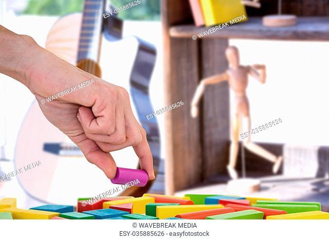 Composite image of cropped hand arranging plastic blocks