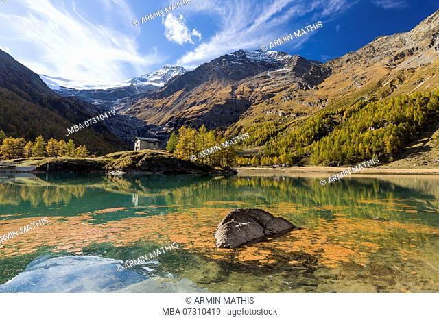 The afternoon sun bathes the area around the reservoir Lago Palü on the Alp Grüm near Poschiavo in an autumnal light, canton Grisons, Switzerland