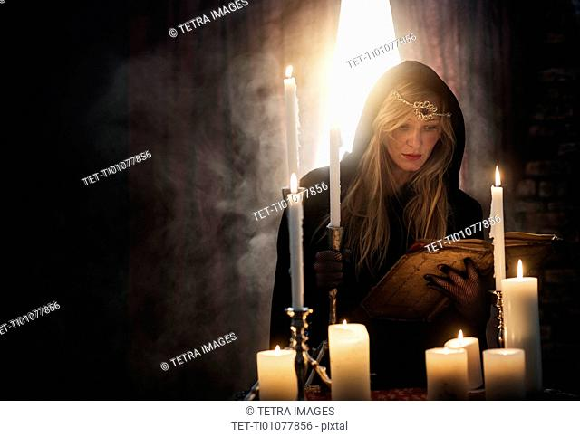 Sorceress reading book in dark room