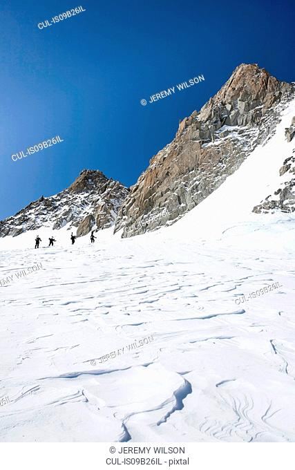 Four male snowboarders hiking up snow-covered landscape, Trient, Swiss Alps, Switzerland
