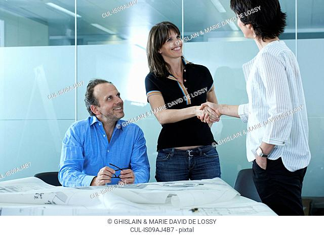 Architect greeting client with blueprints on boardroom table