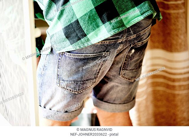 Man in denim shorts, mid section