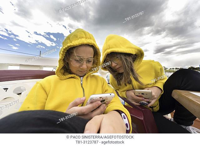 girls looking at a mobile phone at the beach of Alcocebre, Castellon, Spain
