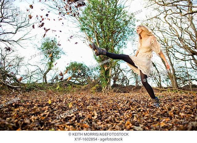a slim blonde woman girl alone in woodland autumn afternoon daytime kicking up dry leaves, UK