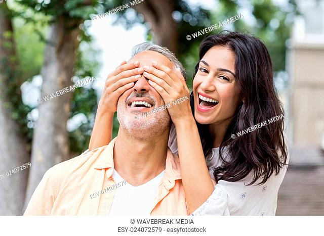 Portrait of woman covering man's eyes