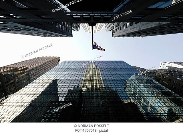 Directly below view of American Flag amidst modern office skyscrapers against sky, New York, USA
