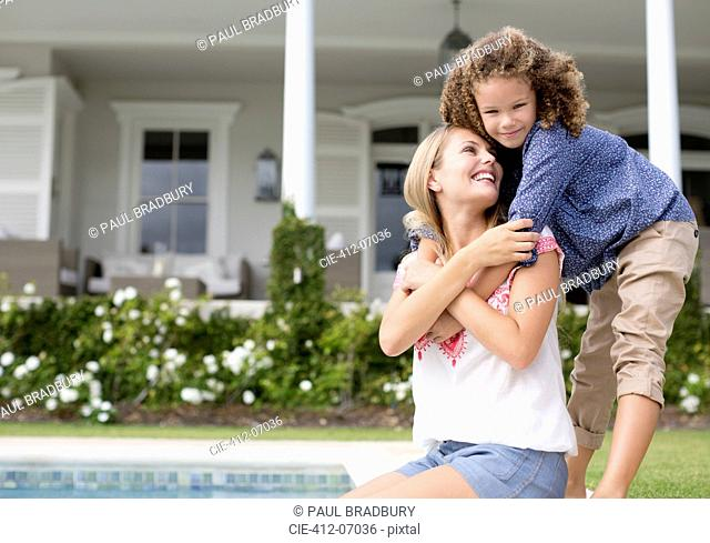 Mother and daughter hugging by swimming pool