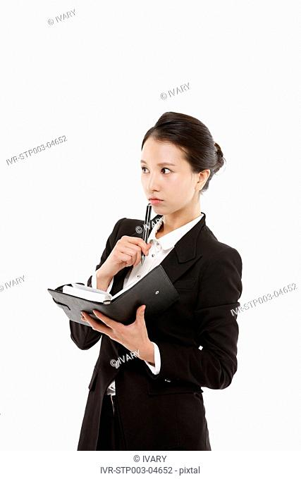 A young businesswoman posing in a studio with a planner and a pen