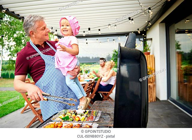 Mature man carrying toddler granddaughter barbecuing at family lunch on patio