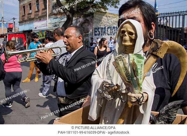 31 October 2018, Mexico, Mexico-City: A supporter of Santa Muerte holds a statue of the patron saint in front of a shrine in the Tepito district while a...