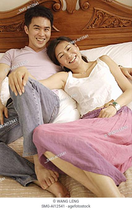 Couple lying in bed, looking at camera