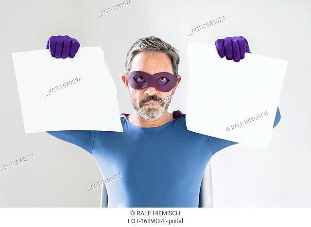 Portrait of superhero holding torn blank placard against white background
