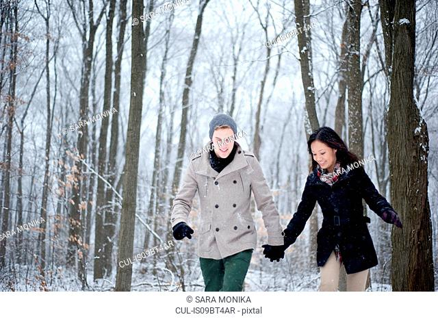 Young couple walking hand in hand in snow covered forest, Ontario, Canada