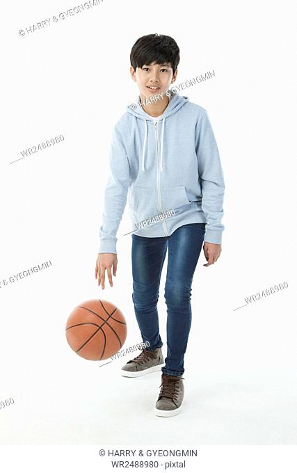 Smiling teenager boy standing dropping a basketball