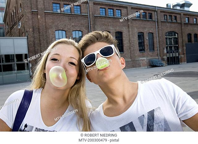 Teenage couple blowing bubble gum