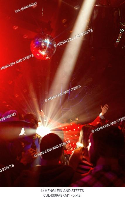 Nightclub scene with people dancing, disco ball, lighting equipment
