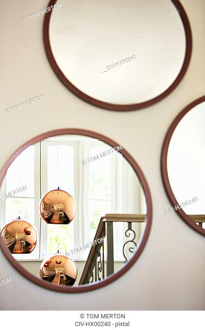 Reflection of copper pendant lights in round mirror