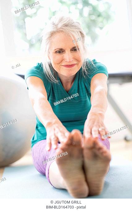 Older Caucasian woman stretching in gym