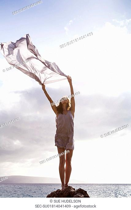 Woman standing on rock near ocean, holding fabric in the wind