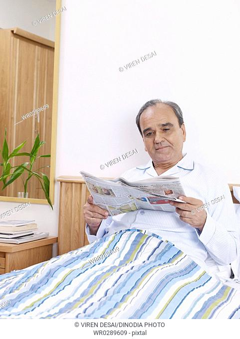 Old man reading newspaper sitting on bed MR702T