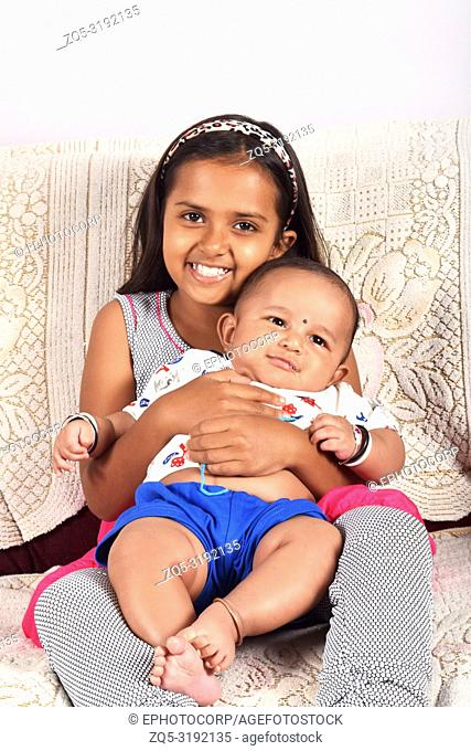 Sister hugging happy baby brother sitting on sofa, Pune, Maharashtra