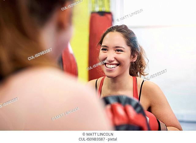 Over shoulder view of female boxer training, punching teammates punch mitt