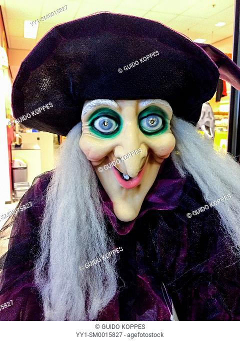Tilburg, Netherlands. A large witch doll on sale in front of a down town store, just before Haloween
