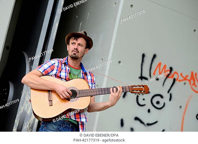 FILE - A file photo dated 27 August 2013 shows street musician Moritz Rabe playing his guitar in Bamberg, Germany, 27 August 2013