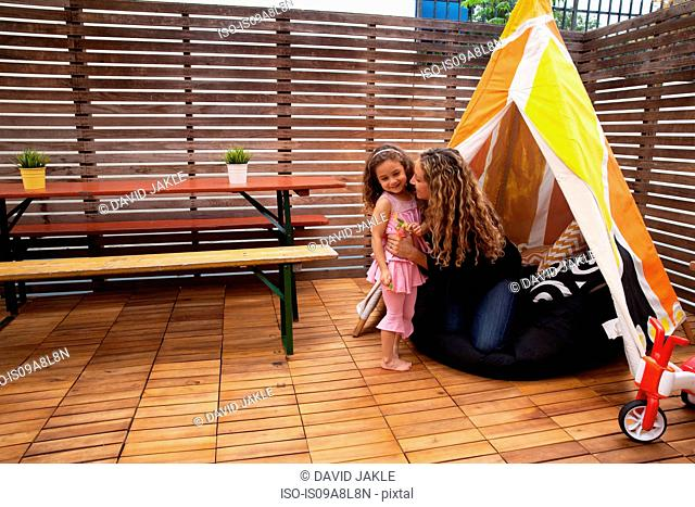 Mother and daughter by tent on patio
