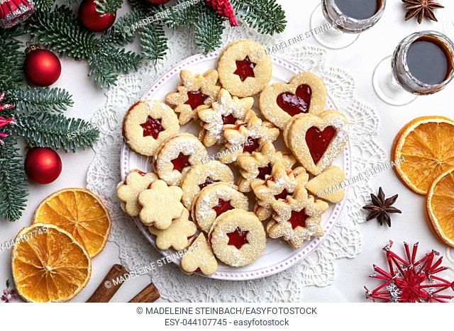Traditional Linzer Christmas cookies filled with strawberry jam arranged on a plate, top view