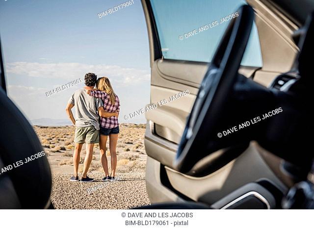 Hispanic couple hugging on remote road