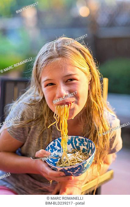 Noodles hanging from mouth of Caucasian girl holding bowl
