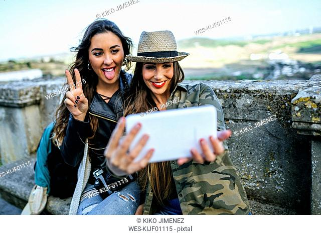 Two happy young women on a trip taking a selfie with a tablet