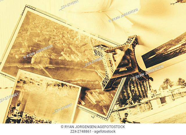 Toned image of Eiffel Tower and photographs on table. Nostalgic Paris moments and mementos