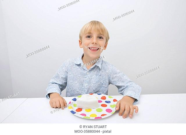 Portrait of happy boy with cake slice in plate on table at home