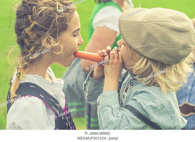 Germany, Saxony, boy and girl together biting off a carrot