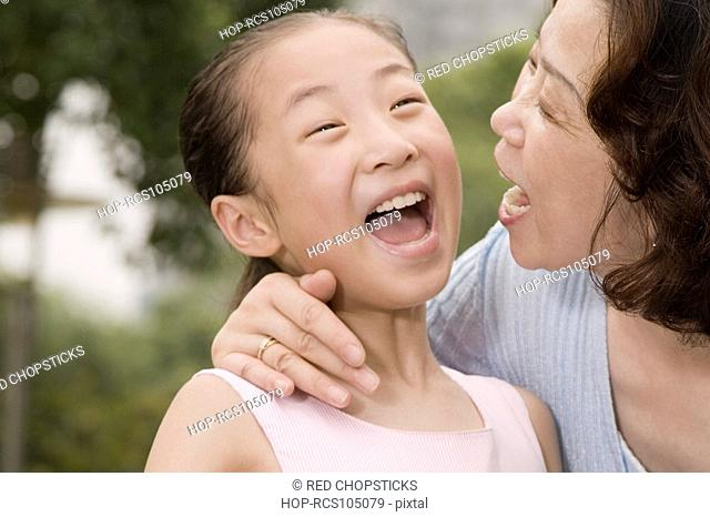 Close-up of a mature woman laughing with her granddaughter